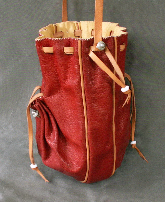 Draw string purse with two side pockets and a side gusset